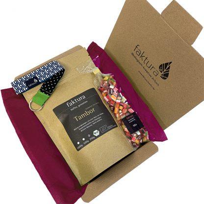 Faktura-Karton mit kleiner Auswahl an Produkten aus der Manufaktur. Dieser beinhaltet 250 Gramm Kaffee Tambor, eine Tüte Bonbon-Mix und einen Schlüsselanhänger aus unserer Textilabteilung