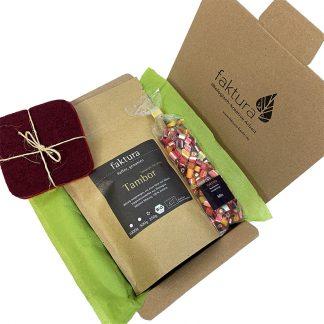 Faktura-Karton mit kleiner Auswahl an Produkten aus der Manufaktur. Dieser beinhaltet 250 Gramm Kaffee Tambor, eine Tüte Bonbon-Mix und ein Filzuntersetzer-Set aus unserer Textilabteilung