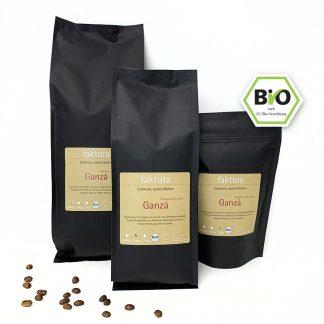 Drei schwarze Tüten Kaffee Ganzá Espresso, ganze Bohne drapiert mit einigen Kaffeebohnen im Vordergrund